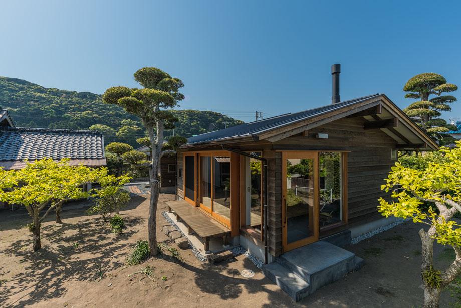 大きな木製サッシに深い軒をかけた家