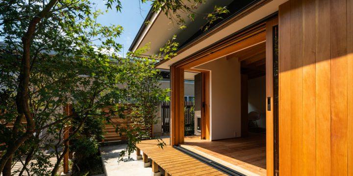 大きな木製サッシの上に深い軒と庇のある家